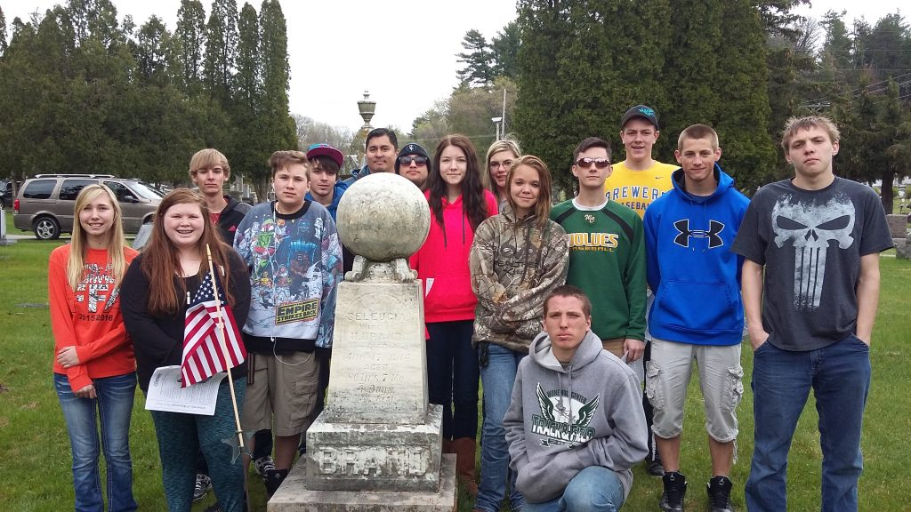 Sophmore Biology class with one of many headstones they cleaned as part of Arbor Day celebration.